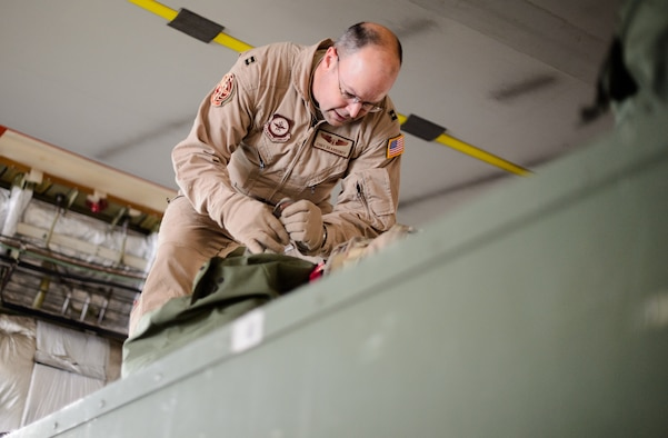 Capt. Cody Deardorff, 10th Expeditionary Aeromedical Evacuation Flight nurse, ties down bags inside of a C-17 Globemaster III Nov. 10, 2015, at Ramstein Air Base, Germany. Deardorff and several other medical personnel helped to save more than 2,500 lives through aeromedical evacuation this year. (U.S. Air Force photo/Staff Sgt. Armando A. Schwier-Morales)