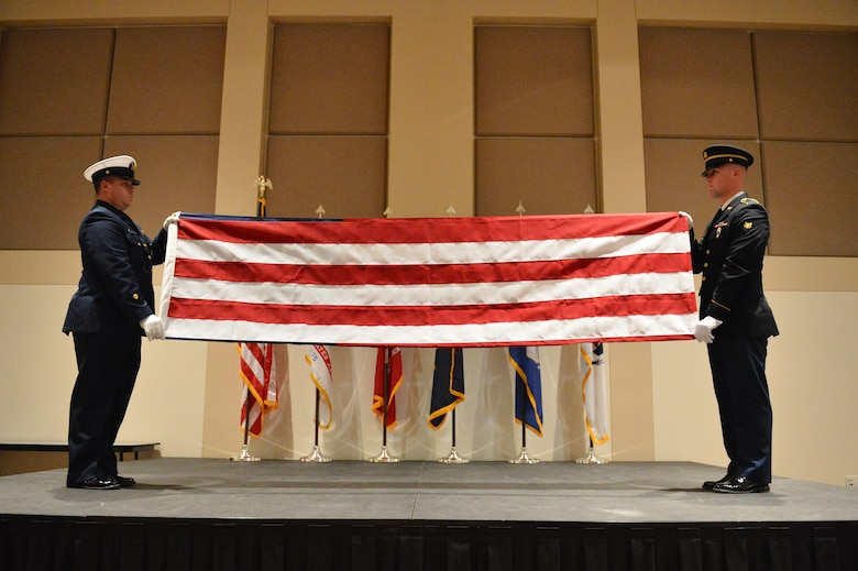 Members of the Aerospace Data Facility-Colorado Joint Color Guard fold a U.S. flag during the Veterans Day ceremony at the Leadership Development Center Nov. 13, 2015, on Buckley Air Force Base, Colo. Aside from the flag-folding ceremony, the event included a guest speaker. (U.S. Air Force photo by Staff Sgt. Darren Scott/Released)