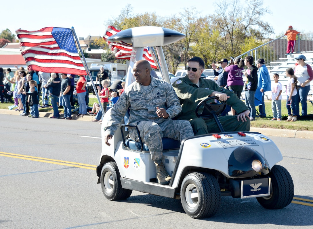 With 552nd Air Control Wing Vice Commander Col. Bradley Bird at the wheel, 552nd ACW Command Chief Master Sgt. Avery Woolridge throws candy as they drive down the parade route in their AWACS-modified golf cart.  (Air Force photo by Kelly White/Released)