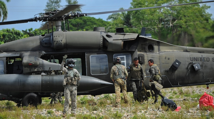 A crew chief with the 1-228th Aviation Regiment signals to Honduran soldiers preparing to disembark for a forward operating location Nov. 4, 2015, in the Gracias a Dios department (state) of Honduras. The 1-228th and members of Joint Task Force-Bravo provided airlift capabilities to the Hondurans as they rotated forces in the area to combat trans-national organized crime organizations in the Honduran borders. (U.S. Air Force photo by Capt. Christopher J. Mesnard/Released)