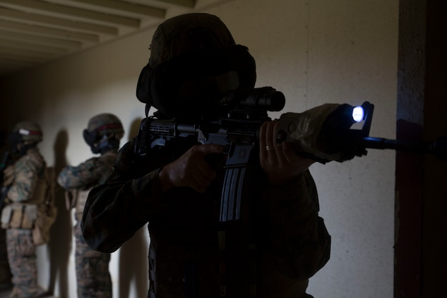 Cpl. Mark McNulty provides security while his fire team searches a Marine from the opposing side in Central Training Area's Combat Town in Okinawa, Japan, Nov. 6, 2015. A fire team of Marines entered and cleared a building with special effect small-arms marking system rounds with an opposing force hiding a hostage. The scenario was conducted on the final day of a three day training event aimed at improving skills clearing buildings. McNulty is from Scranton, Pennsylvania, and is a military policeman with Military Police Detachment, Combat Logistic Battalion 31, 31st Marine Expeditionary Unit.