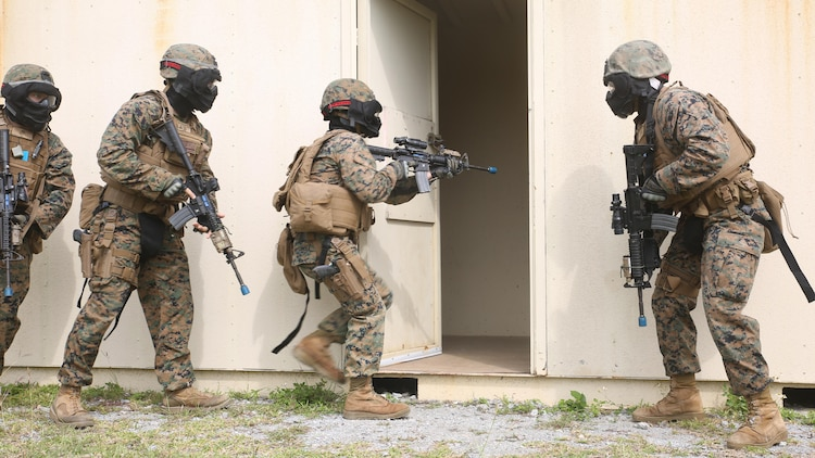 A fire team of Marines, with Military Police Detachment, Combat Logistics Battalion 31, 31st Marine Expeditionary Unit, clear a building with special effect small-arms marking system rounds in Central Training Area's Combat Town in Okinawa, Japan, Nov. 4, 2015. The Marines conducted training over three days, and went through various scenarios to advance the Marines' skills in clearing buildings.