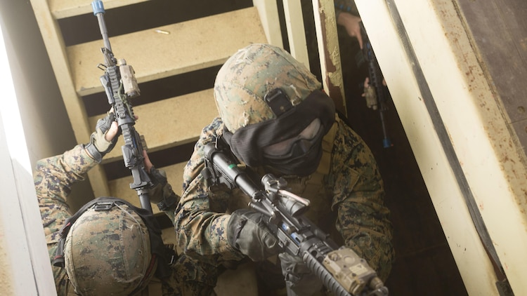 Lance Cpl. Alex Mann, left, and Cpl. Robert Sweeny, right, clear a stairway before entering the second floor as their fire team clears a building Central Training Area's Combat Town in Okinawa, Japan, Nov. 6, 2015. An opposing force hid in the building with a hostage and both sides had special effect small-arms marking system rounds. Mann is from Dunstable, Massachusetts and Sweeny is from Jefferson, New Jersey. Both are military policemen with Military Police Detachment, Combat Logistic Battalion 31, 31st Marine Expeditionary Unit.