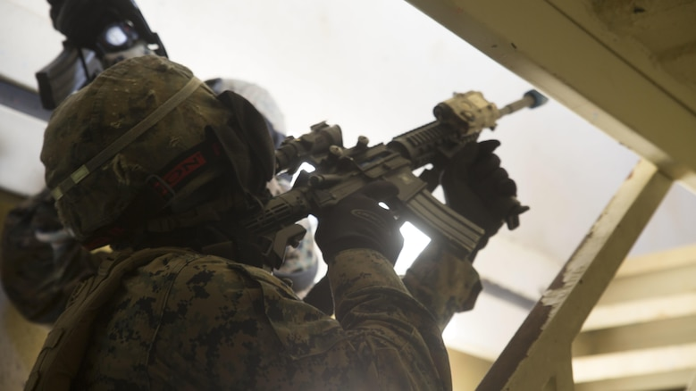 Lance Cpl. Alexis Vergara clears a stairway before his fire team moves to the second floor in a building in Central Training Area's Combat Town in Okinawa, Japan, Nov. 6 2015. The Marines with Combat Logistic Battalion 31, 31st Marine Expeditionary Unit, used special effect small-arms marking system rounds and cleared buildings with opposing forces during a three day training event. Vergara, a native of Chino Hills, California, is a military policeman with Military Police Detachment, CLB 31, 31st MEU.