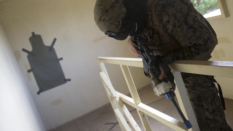 Lance Cpl. David Gamble acts as the opposing force hiding inside a building while a fire team of Marines clear it and search for a hostage in Central Training Area's Combat Town in Okinawa, Japan, Nov. 6, 2015. Both sides used special effect small-arms marking system rounds to create a more realistic environment because they can see where their shots land. Gamble is from Dallas, Texas, and is a military policeman with Military Police Detachment, Combat Logistic Battalion 31, 31st Marine Expeditionary Unit.