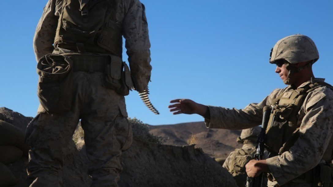 A Marine with Charlie Company, 1st Battalion, 8th Marine Regiment, right, receives ammunition during the counterattack of the Battalion Assault Course, the culminating event for Integrated Training Exercise 1-16 aboard Marine Corps Air Ground Combat Center, Twentynine Palms, Calif., Nov. 6, 2015. The BAC integrates all elements of the Marine Air-Ground Task Force in order to defeat a large simulated enemy force.