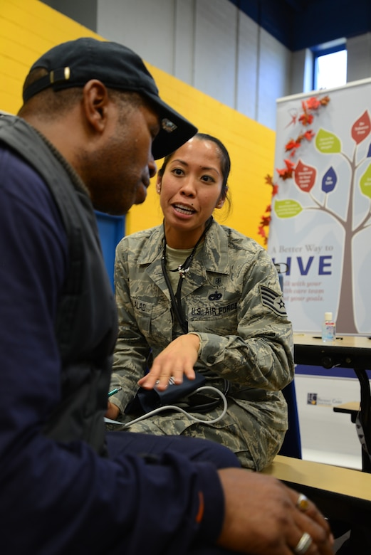 Staff Sgt. Debbie Macalalad, 108th Medical Group, New Jersey Air National Guard, uses the occasion of a blood pressure check to personally connect with homeless veteran William Brown of Parlin, N.J. at the New Jersey Department of Military and Veterans Affairs Stand Down Day at the John F. Kennedy recreation center in Newark, N.J. On Oct. 10, 2015. The stand down day allows the veterans to get much needed care and services from a wide array of state agencies and nonprofit organizations. Members of the 108th Medical Group have been providing care at stand down days for more than 10 years and were providing blood pressure checks as a means to have conversations with the veterans about their overall health and wellness. Stand Down is a military term referring to exhausted combat units that were removed from the battlefront to a place of security and safety for rest and recovery. Today, Stand Downs are grass roots, community-based intervention program to help veterans' battle life on the streets. (U.S. Air National Guard photo by Master Sgt. Carl Clegg, Released)