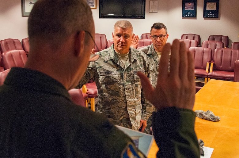 Col. Thomas Coppinger, front, administers the Oath of Enlistment for Master Sgt. Steven Wescott, center, and Master Sgt. Michael Ping to recite in the 108th Wing's conference room at Joint Base McGuire-Dix-Lakehurst, N.J., Sept. 19, 2015. Airmen from the wing can reenlist for an additional 1-6 years. (U.S. Air National Guard photo by Airman 1st Class Julia Pyun/Released)