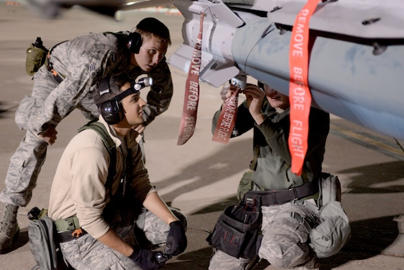 U.S. Air Force Airmen, assigned to 140th Weapons Maintenance Squadron, Colorado Air National Guard, load bombs in preparation for a night flying exercise at Buckley Air Force Base in Aurora, Colo., during the wing wartime readiness inspection Oct. 16, 2015. Weapons have been responsible for loading and unloading bombs, guns and any other weapons on the aircraft. (U.S. Air Force photo by Senior Airman Bobbie Reynolds)