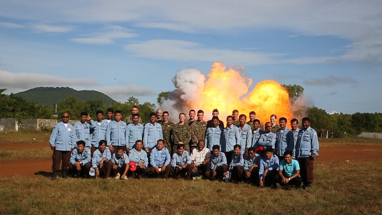 Explosive ordinance disposal U.S. Marines and Cambodian Mine Action Center technicians pose for a picture in front of exploding ordinance at Kampong Chhnang, in the Kingdom of Cambodia, Nov. 5, 2015. U.S Marine EOD trained CMAC in support of the Humanitarian Mine Action program. The program focuses on assisting selected countries in relieving human suffering and in developing an indigenous mine action capability to help with explosive remnants of war.
