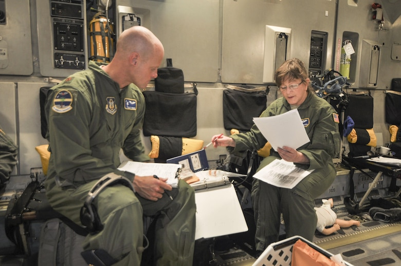 Col. Sunny Gates (right), director of operations for the 315th Aeromedical Evacuation Squadron at Joint Base Charleston goes over medical procedures with Maj. Dale Yarboro on a recent off-station training mission. (U.S. Photo by Maj. Wayne Capps)