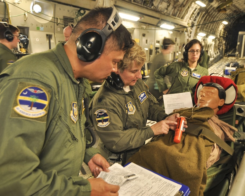 Lt. Col. Angie Trogdon, a flight nurse with 315th Aeromedical Evacuation Squadron at Joint Base Charleston goes over medical procedures with Master Sgt. Robert Jonas on a recent off-station training mission. (U.S. Air Force Photo by Maj. Wayne Capps)