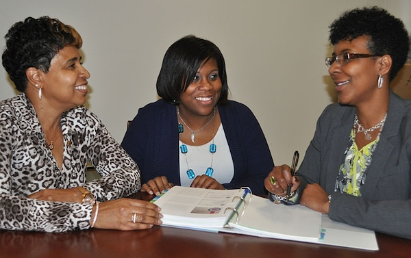 Defense Logistics Agency Equal Employment Opportunity Technician Charnika Hayes, center, discusses with her mentors DLA EEO Staff Director Janice Samuel, left, and DLA EEO Deputy Director Bridget Lanier, right, her new roles and responsibilities during the six-month rotation with DLA EEO.