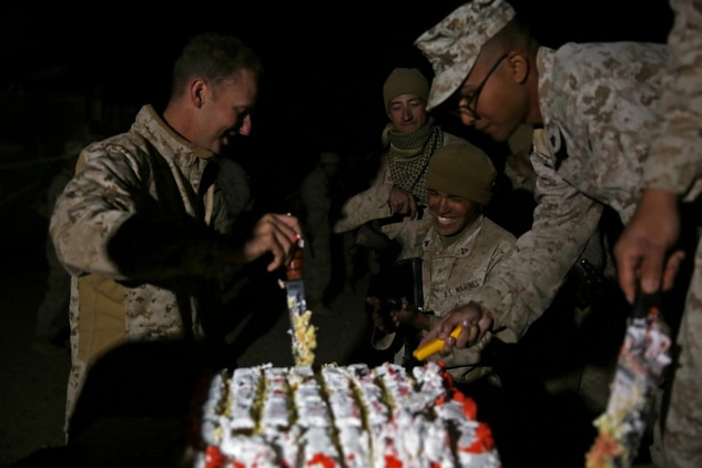 Captain Brian Jaquith, company commander of Co. A, 3rd Assault Amphibian Battalion, 1st Marine Division, cuts and presents cake in celebrate of the Marine Corps' 240th birthday aboard Yuma Proving Grounds, Ariz., Nov. 10, 2015. The Marines and Sailors celebrated the birthday as a culminating event to the 18-day field operation.