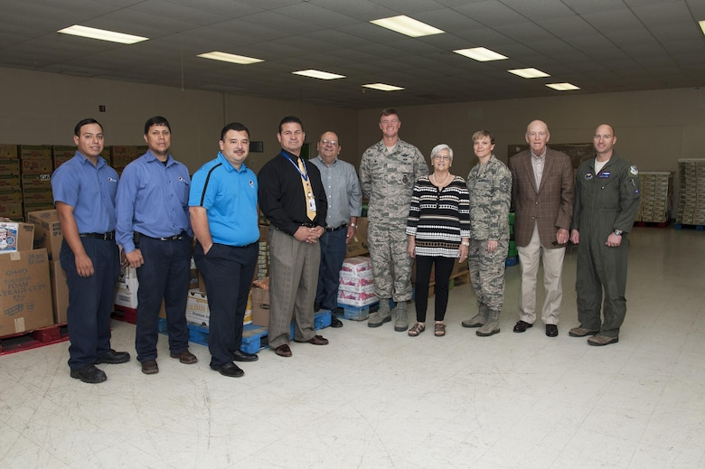 Col. Thomas Shank, 47th Flying Training Wing commander, and Chief Master Sgt. Teresa Clapper, 47th FTW command chief, pose with community leaders, volunteers and Val Verde Loaves and Fishes food pantry staff in front of food donated as part of the Feds Feed Families campaign in Del Rio, Texas, Nov. 12, 2015. Shank and Clapper were on hand to celebrate the handover of more than 24,000 pounds of non-perishable food items collected by the men and women living and working on Laughlin Air Force Base for the local food bank, which helps feed approximately 18,000 families in and around Del Rio each year. (U.S Air Force photo by Staff Sgt. Nathan Maysonet)