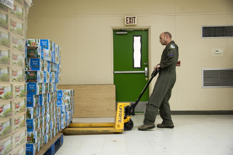 Maj. Derek Flynn, 87th Flying Training Squadron assistant director of operations, moves a pallet of canned goods at the Val Verde Loaves and Fishes food pantry in Del Rio, Texas, Nov. 12, 2015. As part of the Feds Feed Families campaign, Laughlin Air Force Base personnel and their families collected and donated more than 24,000 pounds of non-perishable food items to the food pantry, which is the only local food bank supported by the City of Del Rio, the local school district and Val Verde County. (U.S. Air Force photo by Staff Sgt. Nathan Maysonet)