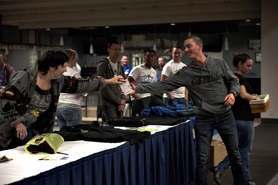 Laurel L. Matus, 17th Training Wing Sexual Assault Prevention and Response victim advocate, hands out an award to a participant during the 4th Annual SAPR Guys Night Out event at the Event Center on Goodfellow Air Force Base, Texas, Nov. 12, 2015. SAPR program officials held the event and gave out many prizes by drawing raffle tickets. (U.S. Air Force photo by Airman 1st Class Caelynn Ferguson/Released)