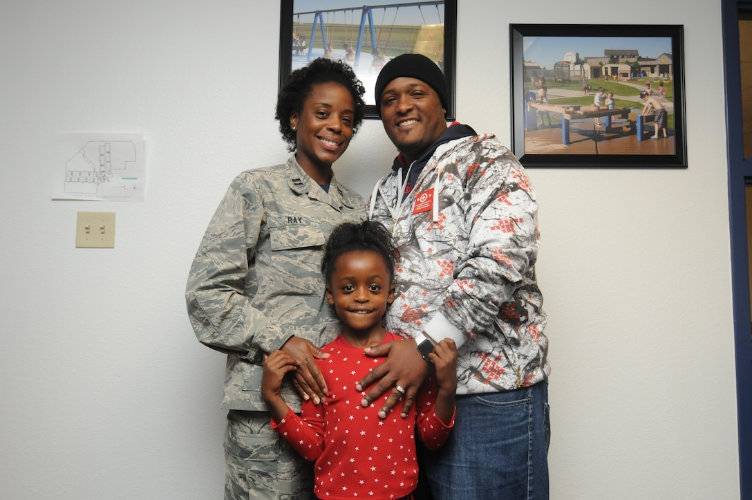 Jayla Ray (center) holds on to her parents, Chaplain (Capt.) Jennifer Ray, 50th Space Wing, and Je'Mahl Ray, Child Development Center Child and Youth Program assistant Friday, Oct. 23, 2015, at the Child Development Center at Schriever Air Force Base, Colorado. Jennifer's decision to become an Air Force Chaplain stirred many changes in Jayla's life, but her family's support and unity has anchored them together. (U.S. Air Force photo/2nd Lt. Darren Domingo)