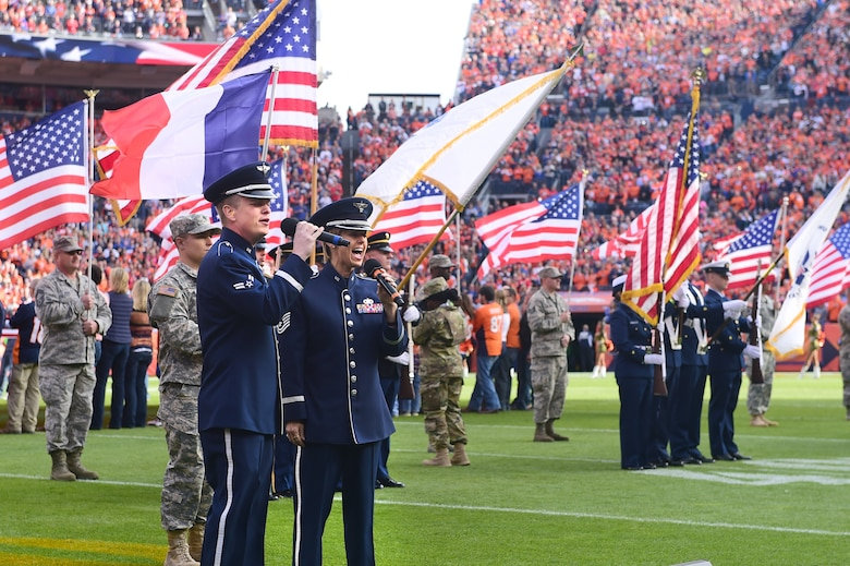 Two members of the U.S. Air Force sing the National Anthem Nov. 15, 2015, at Sports Authority Field at Mile High Stadium, Denver. The Denver Broncos hosted military members at their Salute to Service game against the Kansas City Chiefs. (U.S. Air Force photo by Airman 1st Class Luke W. Nowakowski/Released)