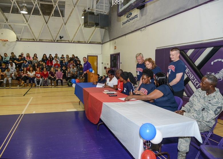 Devyn Cross, Elizabeth Shelton and their parents signed National Letters of Intent to attend the University of Arizona Nov. 13 in the Desert High School Gym while members of the student body cheered them on. (U.S. Air Force photo by Rebecca Amber)