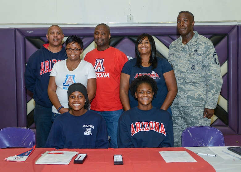Devyn Cross (seated left) and Elizabeth Shelton signed National Letters of Intent to attend the University of Arizona next fall on volleyball scholarships Nov. 13. The students were joined by their parents (left to right) James Culver, Lisa Cross-Culver, James Culver, LaConger Shelton and Chief Master Sgt. Darrell Shelton. (U.S. Air Force photo by Rebecca Amber)