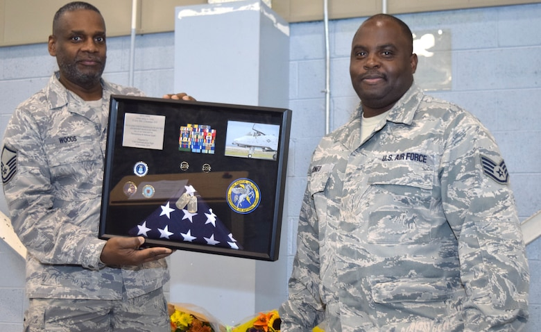 Staff Sgt. Eric Jones, information assurance noncommissioned officer of the 111th Communications Flight, stands with his shadowbox given to him by Master Sgt. Stanley Woods, a cyber surety systems specialist of the111th Attack Wing, during Jone's retirement ceremony at Horsham Air Guard Station, Nov. 14, 2015. Before transitioning into the communications career field, Jones was a crew chief on the A-10 Thunderbolt II. (U.S Air National Guard photo by Master Sgt. Chris Botzum/Released)