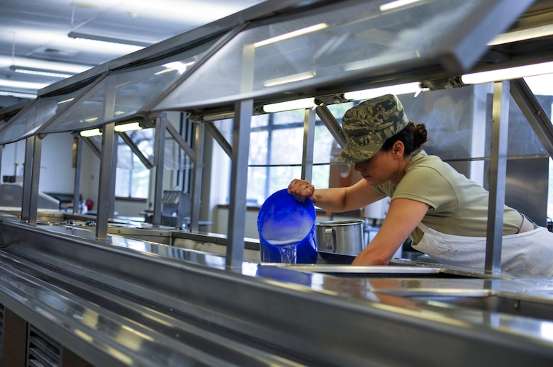 U.S. Air Force Airman 1st Class Tanya L. Brown, a services journeyman with the 182nd Force Support Squadron, Illinois Air National Guard, cleans a salad bar after lunch at the 182nd Airlift Wing in Peoria, Ill., May 2, 2015. Brown – a full-time beautician, farmer, student, wife and mother - enlisted in the Air National Guard at the age of 35. (U.S. Air National Guard photo by Staff Sgt. Lealan Buehrer/Released)
