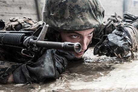 Rct. Tyler C. Cunningham, Platoon 1068, Alpha Company, 1st Recruit Training Battalion, crawls through a combat training course Aug. 4, 2015, on Parris Island, S.C. The course is part of Basic Warrior Training, held during the ninth week of boot camp, which focuses on basic field-related skills all Marines must know. The initial combat training recruits receive will be broadened after boot camp during follow-on training at Camp Lejeune, N.C. Cunningham, 23, is from Enfield, Conn. Parris Island has been the site of Marine Corps recruit training since Nov. 1, 1915. Today, approximately 20,000 recruits come to Parris Island annually for the chance to become United States Marines by enduring 13 weeks of rigorous, transformative training. Parris Island is home to entry-level enlisted training for approximately 50 percent of males and 100 percent of females in the Marine Corps. (Photo by Lance Cpl. Vanessa Austin)