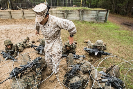 Recruits of November Company, 4th Recruit Training Battalion, maneuver under concertina wire on a combat training course March 24, 2015, on Parris Island, S.C. The course is part of Basic Warrior Training, held during the ninth week of boot camp, which focuses on basic field-related skills all Marines must know. These skills will be broadened during follow-on training at Camp Lejeune, N.C. Parris Island has been the site of Marine Corps recruit training since Nov. 1, 1915. Today, approximately 20,000 recruits come to Parris Island annually for the chance to become United States Marines by enduring 13 weeks of rigorous, transformative training. Parris Island is home to entry-level enlisted training for 50 percent of males and 100 percent of females in the Marine Corps. (Photo by Pfc. Vanessa Austin)