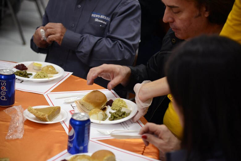 A volunteer serves food at the H-E-B Feast of Sharing at the Del Rio Civic Center in Del Rio, Texas, Nov. 14, 2015. Over 500 volunteers from Laughlin Air Force Base and the local community served more than 2,000 people. (U.S. Air Force photo by Airman 1st Class Brandon May)