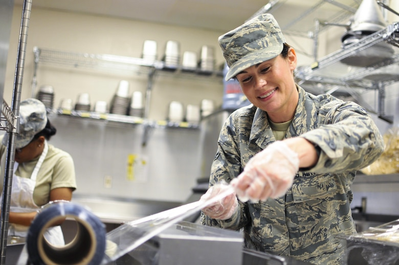 Airman 1st Class Tanya L. Brown, a services journeyman with Illinois Air National Guard's 182nd Force Support Squadron, wraps food after lunch in Peoria, Ill., May 2, 2015. Brown, a full-time beautician, farmer, student, wife and mother, enlisted in the Air National Guard at the age of 35. (U.S. Air National Guard photo/Staff Sgt. Lealan Buehrer)