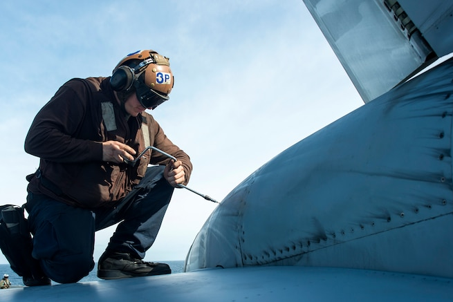 U.S. Navy Airman Anthony Holliday replaces a fastener on an F/A-18E Super Hornet on the flight deck of the USS George Washington in the Atlantic Ocean, Nov. 16 2015. The George Washington is participating in the Southern Seas deployment planned by U.S. Naval Forces Southern Command. U.S. Navy photo by Petty Officer 3rd Class Jaime Marcial