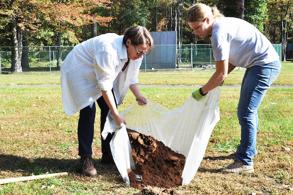 New York District archaeologists Lynn Rakos (left) and Marissa Scarpa (right) refill a hole searching for artifacts on the grounds of Green Brook Middle School in Green Brook, New Jersey, October 21. The plastic ground cover catches dirt from a sifter, limits impact on the excavated area, and makes it easier to refill test holes.