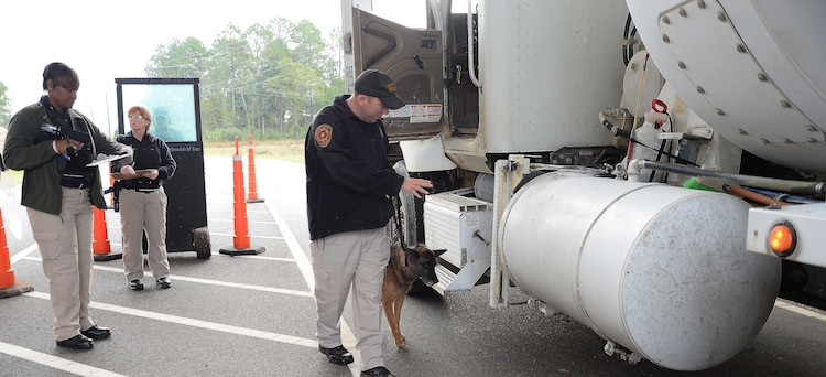 Cpl. Erin Zupko, police officer/K-9 handler, Marine Corps Police Department, Marine Corps Logistics Base Albany, and his military working dog, Meta, walk the perimeter of a commercial vehicle during a checkpoint inspection at the new Mock Road Gate, recently. All commercial vehicles entering the installation are required to go through security protocols before access is granted. Opening of the new entrance, Nov. 16, officially closes the Fleming Road Gate 5 to commercial vehicles and alleviates congestion for early morning commuters to the installation.