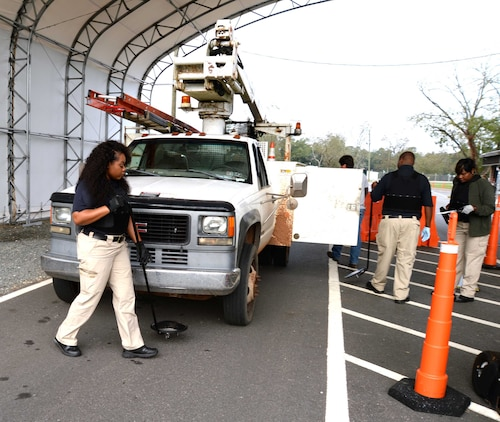 Members of the physical security team, at Marine Corps Logistics Base Albany, inspect a vehicle at the newly-constructed commercial truck entrance at Mock Road, recently. The renovated checkpoint, which was officially opened Nov. 16, was implemented as part of base safety personnel's strategic plan to alleviate early morning traffic congestion created by commercial vehicles at the Fleming Road Gate 5.