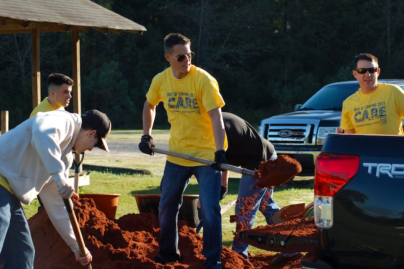Sailors assigned to Naval Nuclear Power Training Command on Joint Base Charleston Weapons Station shovel mulch while beautifying a YMCA baseball field in Summerville, S.C., Nov. 13, 2015. More than 3,500 NNPTC staff and students volunteered during the 2015 Trident United Way Day of Caring. (U.S. Navy photo / Chief Machinist's Mate Jody Greenhill)