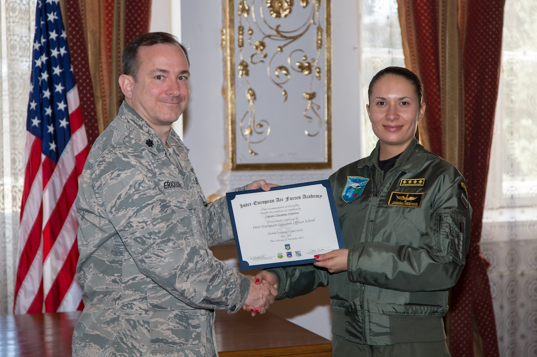Lt. Col. Christopher Erickson, IEAFA Commandant, awards a certificate of completion to Captain Zhasmina Hristova, Bulgarian Air Force, during graduation of the first ever IEAFA combined international officer and NCO PME course graduation in Sofia, Bulgaria, Nov. 13, 2015. Twenty-three students from Bulgaria, Czech Republic, Estonia, and Hungary participated in this inagural course. (U.S. Air Force photo/SMSgt Travis Robbins/Released)