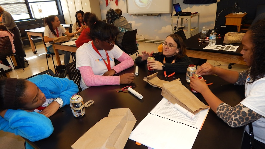 Dr. Rita Peterson, a volunteer at Wright-Patterson Air Force Base, helps (L-R) Ron'nea Judkins, Ashley Harris and Amirra Rankin during the 'STEM-ulate Your Mind: Girls RULE!' event on base Nov.7