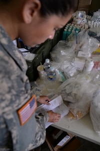 U.S. Army Sgt. Stephanie Tucker, Joint Task Force-Bravo radiologist technician, looks through prescription papers during a medical partnership exercise in the Olancho District, Honduras, Nov. 14, 2015. Tucker is part of the medical element at Soto Cano Air Base and augmented the pharmacy during her  time in Olancho. (U.S. Air Force Photo by Senior Airman Westin Warburton/Released)