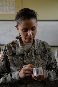 U.S. Army Sgt. Stephanie Tucker, Joint Task Force-Bravo radiologist technician, provides support as she augments a stand-up pharmacy at a medical partnership exercise in the Olancho Department, Honduras, Nov. 14, 2015. Tucker, a Dallas, Texas native, is part of the medical element at Soto Cano Air Base and also participated in a medical readiness training exercise the two previous days. (U.S. Air Force Photo by Senior Airman Westin Warburton/Released)