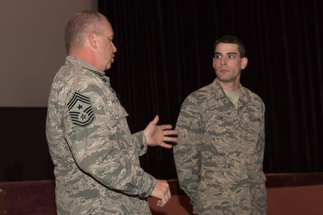 U.S. Air Force Chief Master Sgt. James W. Hotaling, command chief master sergeant of the Air National Guard presents a coin to Airman Basic Skylar Orr, Nov. 8, 2015 in Cheyenne, Wyoming. Hotaling gave a special message to Orr, who is a recent basic training graduate with honors and a cyber operator assigned to the 153rd Command and Control Squadron, Wyoming Air National Guard. (U.S. Air National Guard photo by Tech. Sgt. John Galvin/released)