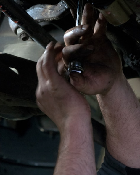 Retired Tech. Sgt. Timothy Staples removes a bolt from the underside of a truck Nov. 13, 2015, in the Auto Skills Shop on F.E. Warren Air Force Base, Wyo. The Auto Skills Shop provides tools and resources that many don't have access to at home. (U.S. Air Force photo by Senior Airman Brandon Valle)