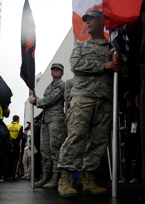 """Master Sgt. Timothy Bolick, 61st Aircraft Maintenance Unit F-35 specialist training monitor, and Airman First Class Katliyn Straight, 56th Medical Operations Squadron medical technician, holds the driver's flag during the opening ceremony of the Quicken Loans Race for Heroes 500 at the Phoenix International Raceway, Ariz., Nov. 15, 2015. For the eight racers racing for the final four slots of """"The Chase,"""" an Airman was chosen to hold that driver's flag. (U.S. Air Force photo by Senior Airman Devante Williams)"""