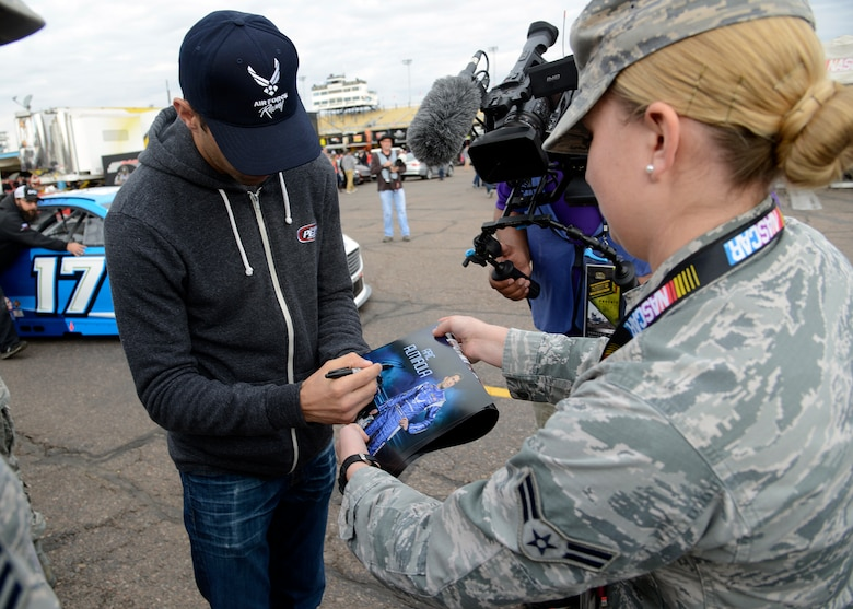 Aric Almirola, NASCAR driver, signs Airman First Class Kaitlyn Staight, 56th Medical Operations Squadron medical technician's, poster during their visit through the garages at the Quicken Loans Race for Heroes 500 at the Phoenix International Raceway, Ariz., Nov. 15, 2015. Almirola talked with the Airmen and autographed gear. (U.S. Air Force photo by Senior Airman Devante Williams)