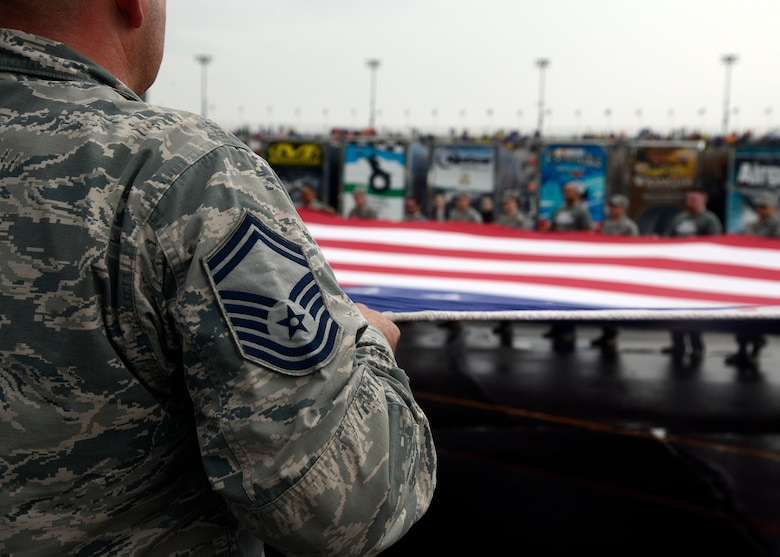 Luke Air Force Base Airmen and military veterans hold the American flag during the singing of The Star Spangled Banner at the opening ceremony of the Quicken Loans Race for Heroes 500 at the Phoenix International Raceway, Ariz., Nov. 15, 2015. Veterans, active military members and their families were front and center for the race as NASCAR honor their service and sacrifice for the nation. (U.S. Air Force photo by Senior Airman Devante Williams)