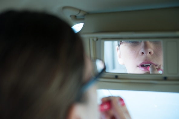 Senior Airman Kyla Gifford, 30th Space Wing photojournalist, applies lipstick while driving her car Oct. 29, 2015, Vandenberg Air Force Base, Calif. According to statistics from the National Highway Traffic Safety Administration, nine people are killed every day, and more than 1,153 people are injured in crashes that involve a distracted driver. (U.S. Air Force photo by Michael Peterson/Released)