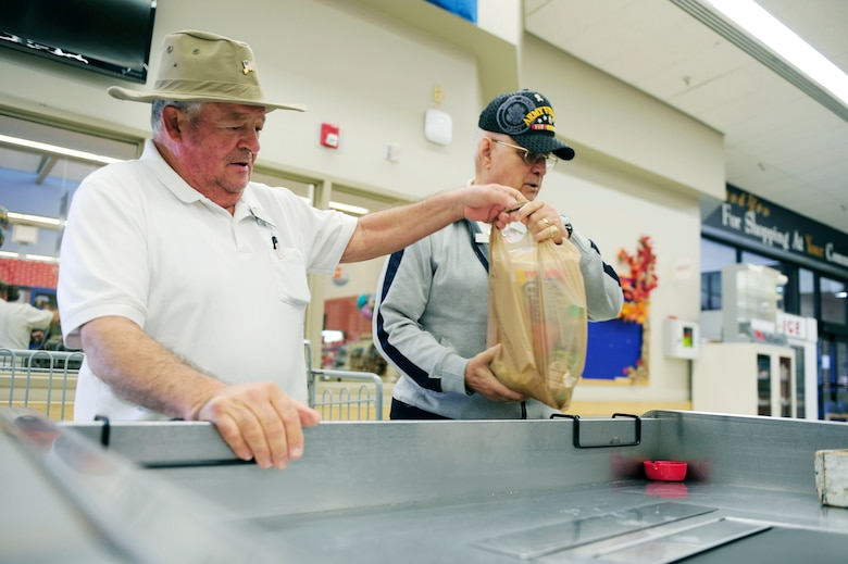 Retired Army Staff Sgt. Robert Michaud and retired Sgt. 1st Class Richard Estes, Vandenberg Commissary baggers, bag groceries, Nov. 18, 2015, Vandenberg Air Force Base, Calif. Michaud and Estes are military veterans who continue to serve in the commissary. (U.S. Air Force photo by Staff Sgt. Jim Araos)
