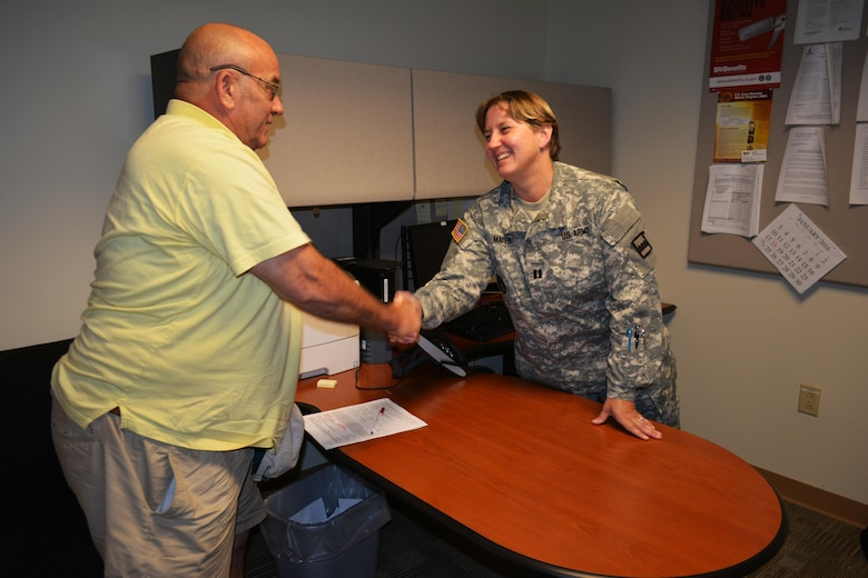 Carl Barnes, a former sergeant who served seven years in the Army Signal Corps, thanks Capt. Tanya Mayes, a military justice and admin law attorney, assigned to the 80th Training Command Office of the Staff Judge Advocate, for the legal assistance she provided to him at Hunter Holmes McGuire VA Medical Center, Richmond, Va. Staff members of the 80th TC OSJA volunteer their services once a month at the medical center helping Wounded Warriors and veterans who qualify for legal benefits. Mayes lead an effort to establish the clinic after her husband, Raymond Pacheco, a nurse at the medical center, told her that a significant number of his patients needed legal assistance.