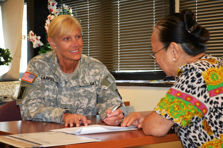 Lt. Col. Phyllis Carpenter, deputy 80th Training Command Staff Judge Advocate, provides legal advice the spouse of a veteran at Hunter Holmes McGuire VA Medical Center, Richmond, Va. Staff members of the 80th TC Office of the SJA volunteer their services once a month at the medical center helping Wounded Warriors and veterans who qualify for legal benefits.