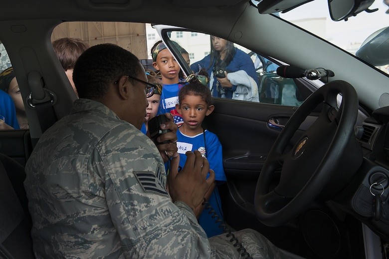 U.S. Air Force Staff Sgt. Darren Harris, 18th Security Forces Squadron, shows children how the radio on the patrol car works at Skoshi Warrior Nov. 14, 2015, at Kadena Air Base, Japan. More than 200 children participated in this annual event, meant to show children their parents' deployment process and to see different aspects of military jobs. (U.S. Air Force photo by Airman 1st Class Corey M. Pettis/Released)